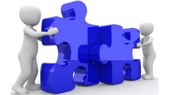 Two white figures putting two blue puzzle pieces together