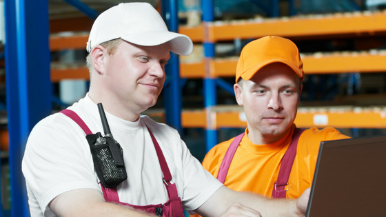 Two men working in a warehouse looking at a laptop