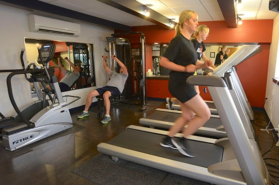 Keller workout room with workout equipment and mirrors, man lifting weights, two women running on treadmills
