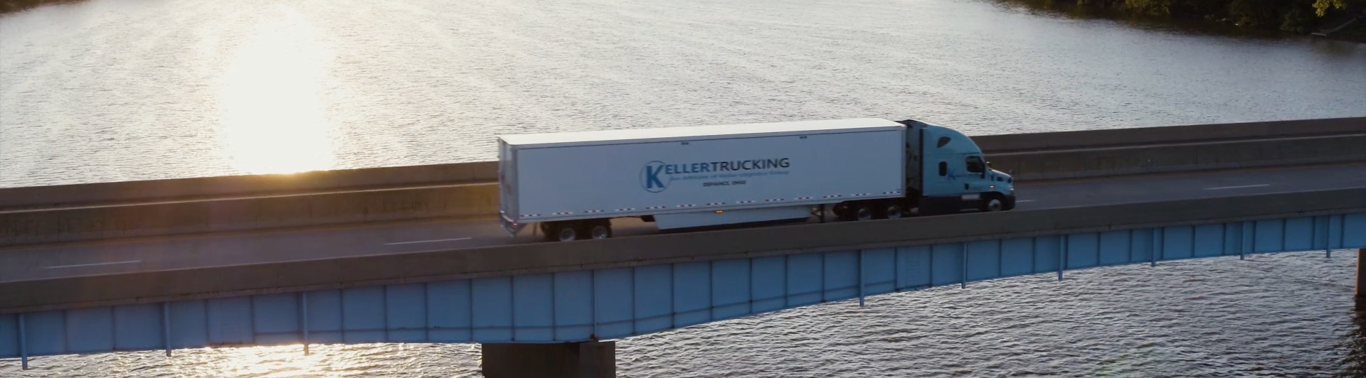 Overhead view of Keller truck crossing bridge over river with sunrise reflecting on water