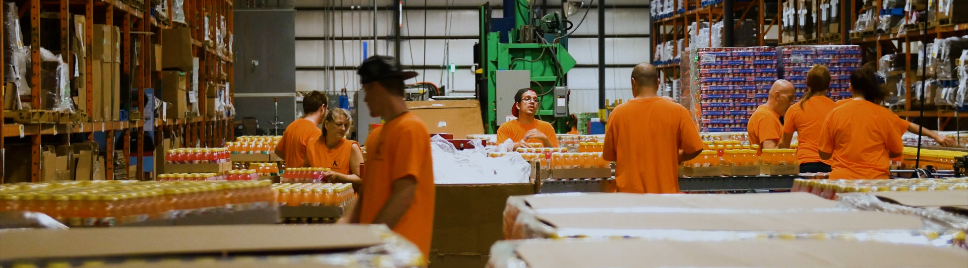 Workers at Packaging facility performing contract packaging services of bundling orange beverage bottles