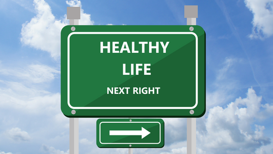 Green street sign says Healthy Life Next Right with arrow pointing right with blue sky with white clouds background