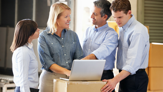 Two women and two men gathered around a laptop sitting on a cardboard box in a warehouse setting