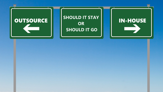 Green highway signs with text- Outsource with arrow left, Should It Stay Or Should It Go, In-House with arrow right