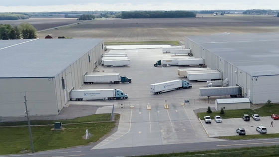 Warehouses on left and right with trucks in docks