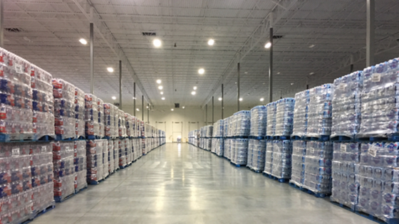Isle in a warehouse with shrink wrapped product stacked on both sides