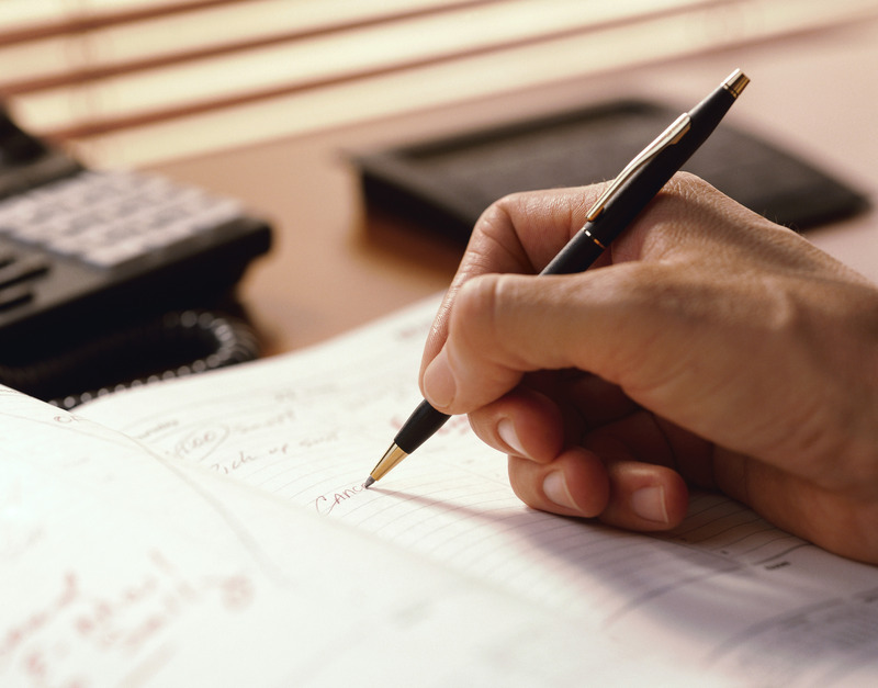Hand with pen writing on paper at an office desk